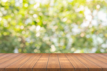 Empty wood table on blurred background copy space for montage your product or design , Blank brown board with abstract blurred green background.