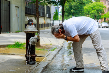 Man during a strong heat temperature is refreshed with Fire hydrant water