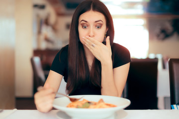 Woman Feeling Sick While Eating Bad Food in a Restaurant