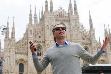 Caucasian male tourist with smartphone near Milan Cathedral, Italy. Concept of modern technology, fast Internet and landmarks.