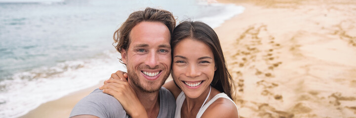 Wall Mural - Tourists on beach Smiling beautiful young multiracial couple taking selfie on vacation panoramic banner crop. Asian woman, Caucasian man.
