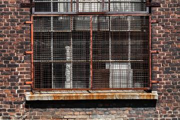 Verrostetes Fenstergitter an Backsteinhaus