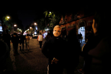 A supporter of presidential candidate Andres Manuel Lopez Obrador celebrates in Mexico City wearing a mask depicting him in Mexico City