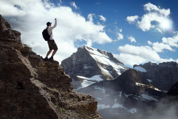 Adventurer shouts victorious celebration while overcoming and conquering challenge on a mountain top