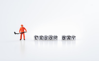 Labor day concept. Word labor day on metal cubes with miniature worker on white background