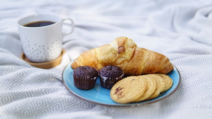 croissants, biscuits and coffee on a picnic overlay