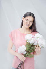 portrait of a young woman with a bouquet of peonies