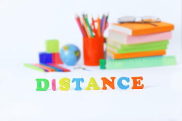 word distance on blurred background of school supplies .photo with copy space