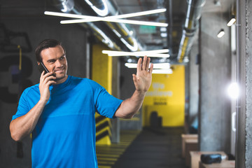 Portrait of outgoing male athlete talking by cellphone while gesticulating hands before training in gym