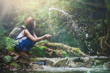 Young hiking lady washing her hands in the fresh cool water of a mountain stream. Wall mural