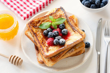 French toast with berries and honey on white plate. Tasty breakfast