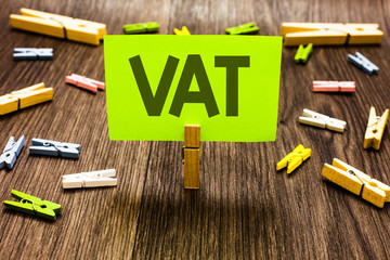 Writing note showing Vat. Business photo showcasing Consumption tax levied on sale barter for properties and services Clips art board creative ideas paper paperclip holding wood shadow.