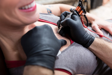 Close-up of the hands of a skilled artist using a modern machine, while making the contour of a cool tattoo on the chest of a female client