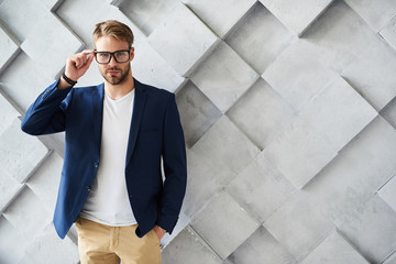 Waist up portrait of handsome stylish man standing and touching the rim of spectacles. He is keeping his hand in pocket while looking straightforward with assurance. Copy space in right side