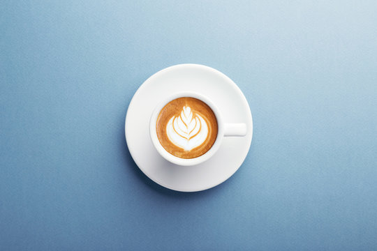 A cup of cappuccino with beautiful latte art on blue background. Top view, central composition.