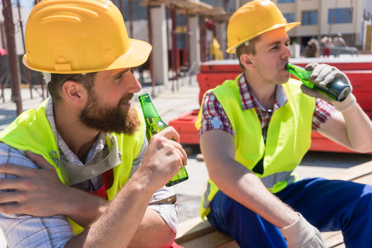 Two young workers smiling, while drinking a cold alcoholic or non-alcoholic beer during break at work on the construction site in a sunny day of summer