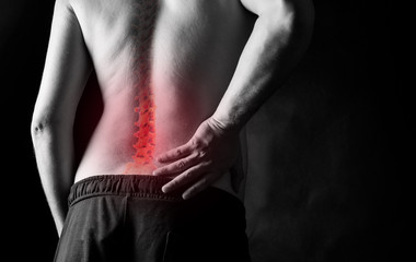 severe back pain. the man holds on to his back