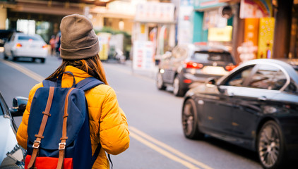 Back side asian woman travel backpack walking in the city at Taipei,travel concept background.vintage tone.