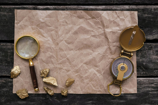 Blank crumpled page with copy space for treasure map, compass, magnifying glass and golden nuggets on old adventure table background.