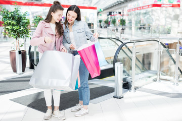 Two happy shoppers showing one another their paperbags with purchase while standing by escalator in the mall