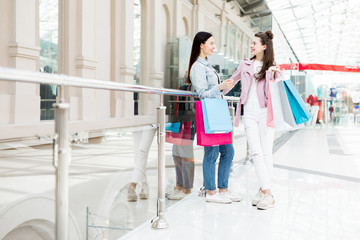 Two cute females in casualwear having talk about what they bought on sale in the mall