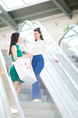 Two smart girls with paperbags standing on steps of escalator and talking after shopping in the mall