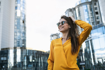 Enjoying success. Confident young woman is relaxing outdoor in city. She is touching her hair elegantly and smiling. Copy space