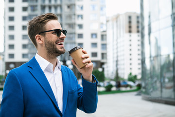 Excited young man is drinking coffee while relaxing in city. He is looking at office building and laughing. Successful job concept. Copy space