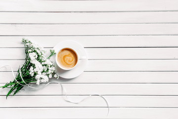 Morning. Cup of coffee on a wooden white background and white flowers. Flat lay, top view, copy space