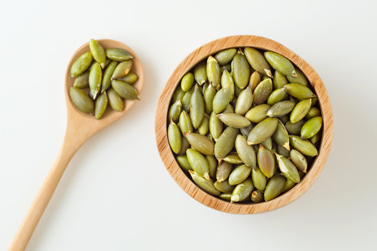 Pumpkin seeds in wooden bowl and spoon on white background