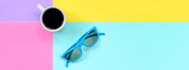 Small white coffee cup and blue sunglasses on texture background of fashion pastel blue, yellow, violet and pink colors paper in minimal concept