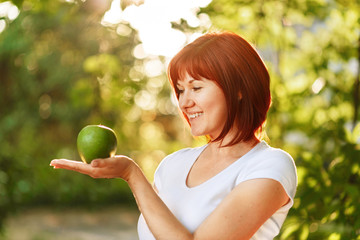 Red-headed young woman looking at green apple on her palm and smiling. Mixed race woman with an apple outdoor in summer sun light. Healthy nutrition concept