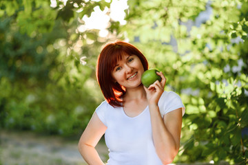 Happy young woman in a white shirt posing with green apple outdoor. Healthy nutricion concept