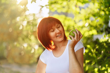 Smiling young woman with an apple in her hand in a golden backlight. Beautiful female in white shirt with big apple. Summer healthy meal