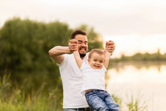 Father and son playing together in a park. Dad is raising the boy up in the air like a big swings. The boy is happy and smiling. Father and son leisure concept