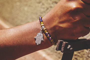 Male hand wrist with colorful bracelet and hamsa silver pendant