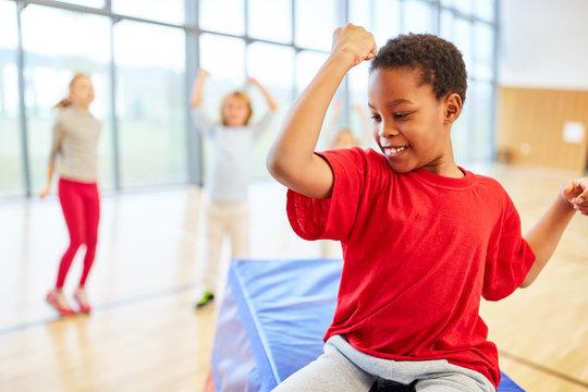 Sportlicher Junge zeigt seine Muskeln