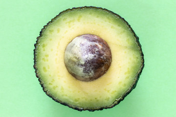 Opened avocado isolated on a green background