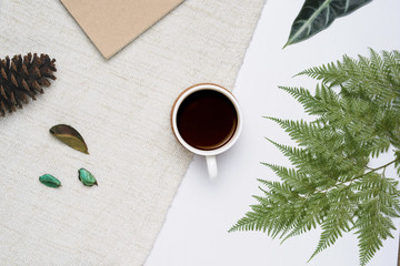 Cup of coffee on white wooden and brown yarn background with tropical fern leaves. Minimal flat lay, top view.