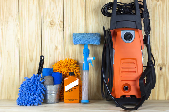 Car wash equipment or car cleaning product such as microfiber tank and pressure washer and glass cleaner and brush with mitts and etc, on wooden table.