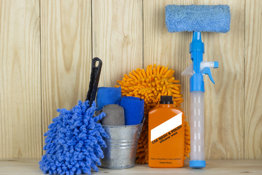 Car wash equipment or car cleaning product such as microfiber tank and  glass cleaner and brush with mitts and etc, on wooden table.