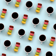 A pattern of many colorful dessert cake macaroon and coffee cups on trendy pastel blue background top view. Flat lay composition