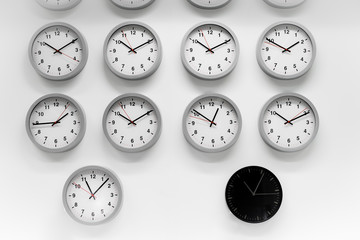 Many White clock and a black classic round wall clock . Different concepts of time