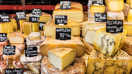 Different cheeses on the counter of a small store at the market. Paris, France