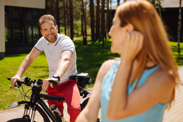 Happy life. Cheerful man riding a bike while looking at his wife and resting outdoors
