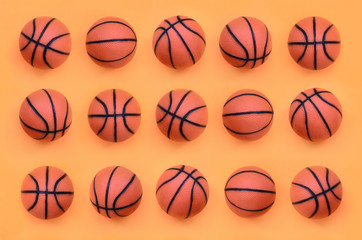 Many small orange balls for basketball sport game lies on texture background of fashion pastel orange color paper in minimal concept