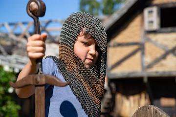 A young boy disguised as an unblemished knight with a sword, shield and  basinet.