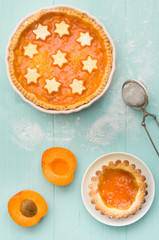 Two homemade apricot cakes on turquoise wooden background.; :