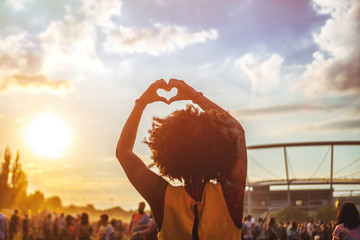Young African American woman at summer holi festival make heart symbol by hands, back view