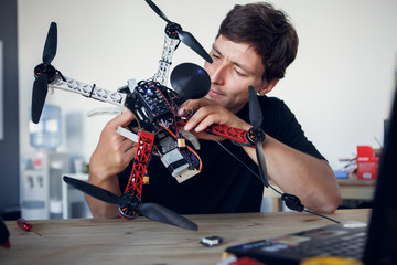Image of young engineer fixing square copter at table